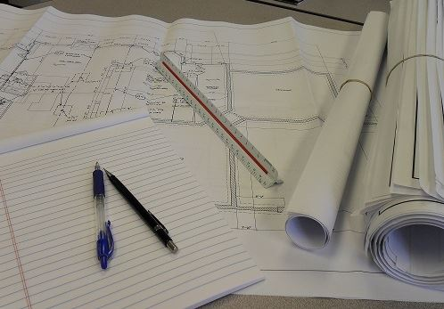 Drafting materials and blueprints sit on a table.